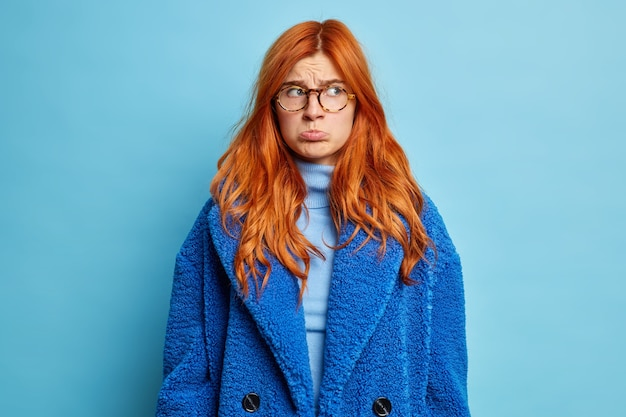 Young displeased woman purses lips and looks with sullen expression aside dressed in turtleneck and blue winter coat.