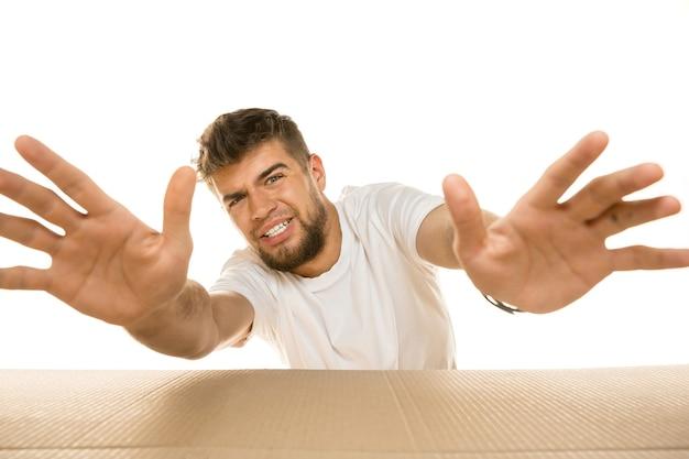 흰색 벽에 고립 된 가장 큰 우편 패키지를 여는 젊은 dissapointed 남자