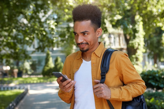 Young dissatisfied dark skinned guy, chatting on the phone with his friends and walking at the park, looking from under his forehead with resentful expression, his girlfriend is late again.