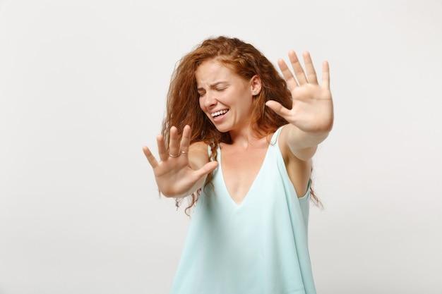 Giovane donna rossa insoddisfatta in abiti casual in posa isolata su sfondo bianco. concetto di stile di vita della gente. mock up copia spazio. in piedi con le mani tese, mostrando il gesto di arresto con i palmi.