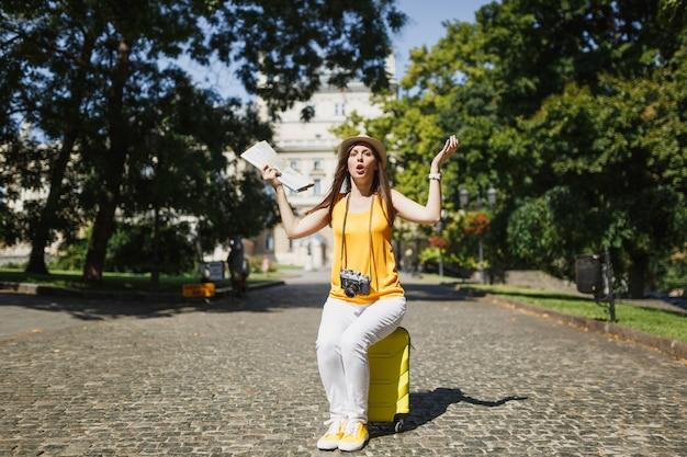 노란색 옷을 입은 젊은 여행자 관광 여성이 여행가방에 앉아 도시 지도를 들고 야외에서 손을 펼치고 있습니다. 주말 휴가를 여행하기 위해 해외로 여행하는 소녀. 관광 여행 라이프 스타일.