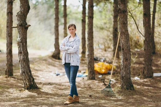 평상복을 입은 젊은 불만족스러운 여성이 흩어져 있는 공원이나 숲에서 손을 접고 청소용 쓰레기를 접었습니다. 환경오염 문제