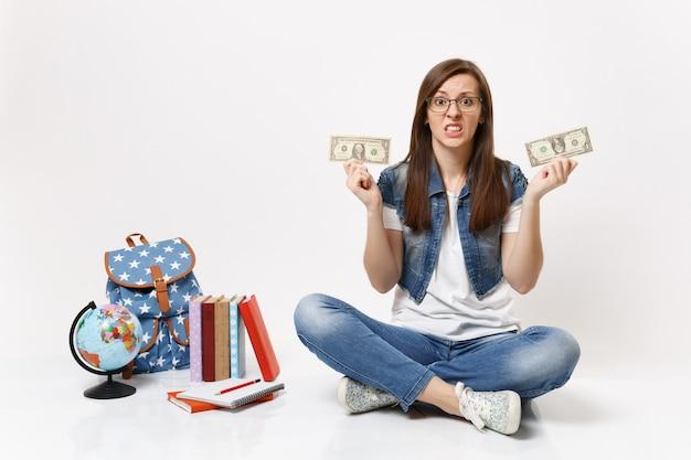 Молодая неудовлетворенная студентка держит долларовые купюры наличными деньгами, чувствуя стресс из-за отсутствия денег, сидит рядом с книгами в рюкзаке с глобусом