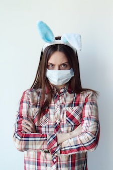 Young dissatisfied woman wearing bunny ears and protective mask