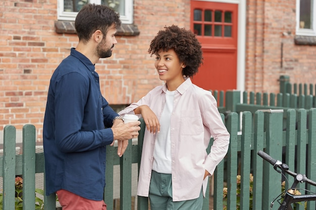 Молодая разноплановая пара встречается на сельской улице, стоит возле зеленого забора и кирпичного дома, позитивно разговаривает