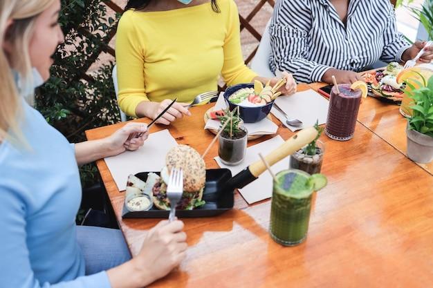 レストランのテラスで屋外で朝食をとっている若い多様な友人-中央の女の子の手に焦点を当てる