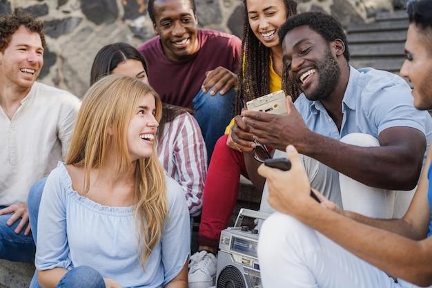 街の屋外でラジカセステレオで音楽を聴くのを楽しんでいる若い多様な人々-カセットを持っているアフリカ人男性に焦点を当てる