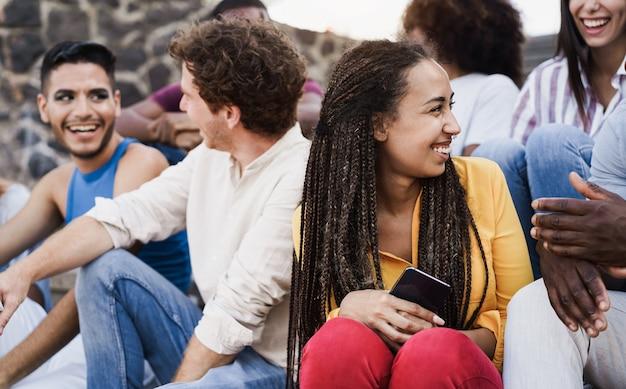 도시에서 야외에서 즐거운 시간을 보내는 다양한 젊은이들 - 아프리카 여성의 얼굴에 초점