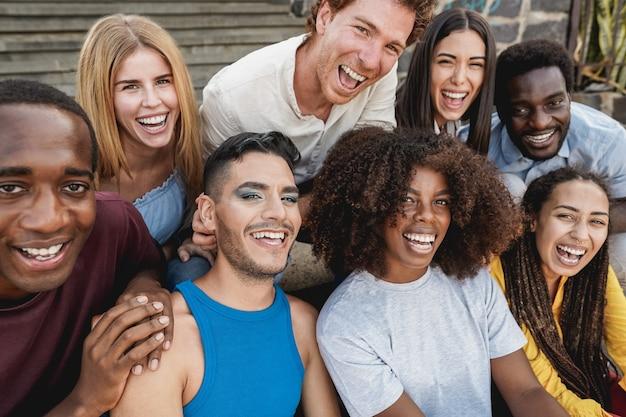 一緒に笑う屋外を楽しんでいる若い多様な人々-ゲイの男性の顔に焦点を当てる