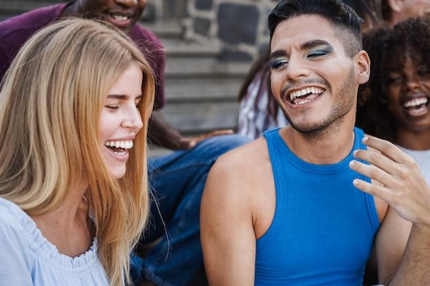 一緒に屋外で笑うのを楽しんでいる若い多様な人々-ゲイの男性の顔に焦点を当てる