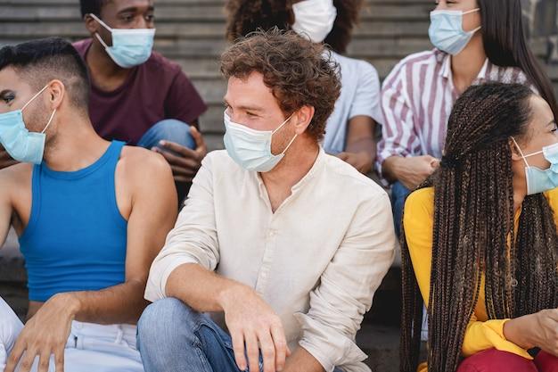 街の屋外で防塵マスクを着用して一緒に笑う若い多様な人々-センターマンの顔に焦点を当てる