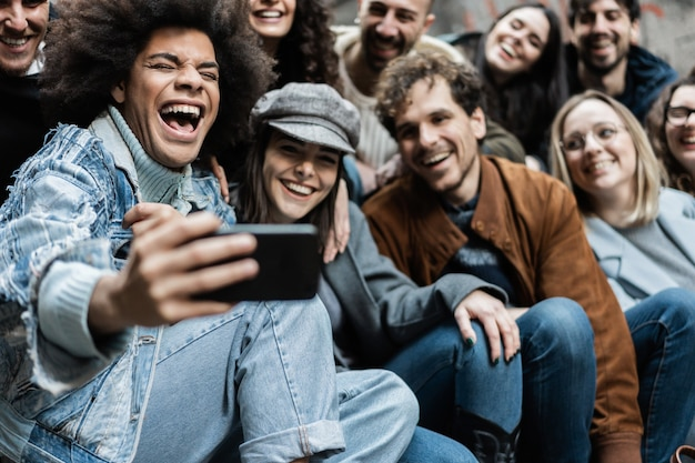 Young diverse people using mobile phones outdoor in the city - main focus on african man face