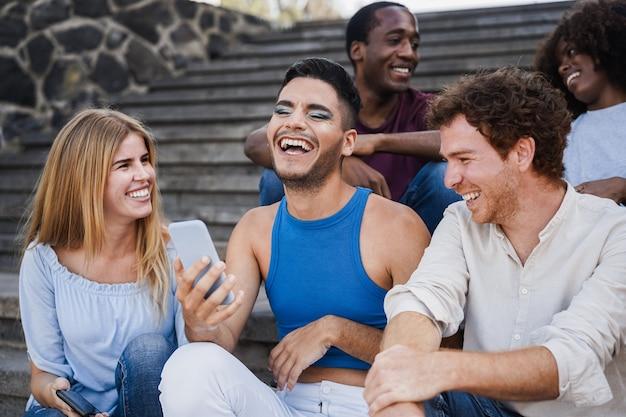 街の屋外で携帯電話を使用している若い多様な人々-トランスジェンダーの男性の顔に焦点を当てる