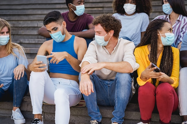 Young diverse people using mobile phones wearing safety mask outdoor in the city - focus on gay man face