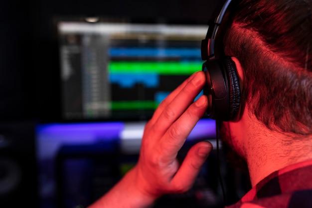 若いdjは、ステレオスタジオの職場でソングミキサーとマイクを使用して新しいトラックを録音しています