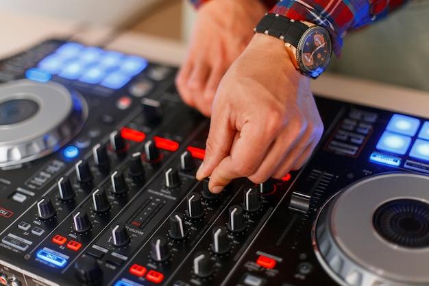 젊은 dj 남자는 오디오 컨트롤러에서 작동합니다. 믹서. 음악 세트