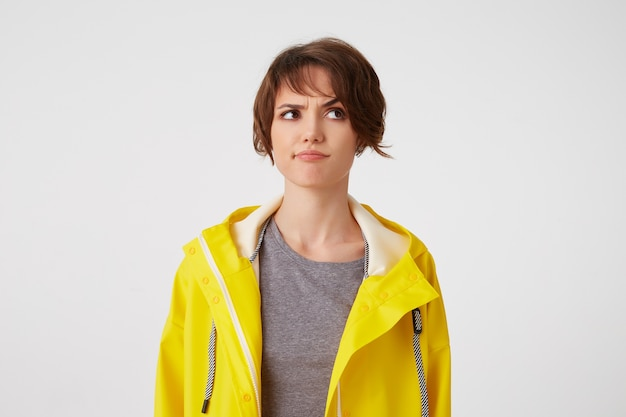 Young dobting short-haired woman in yellowrain coat, frowning looks away, stands over white background, looks discontent and doubting.