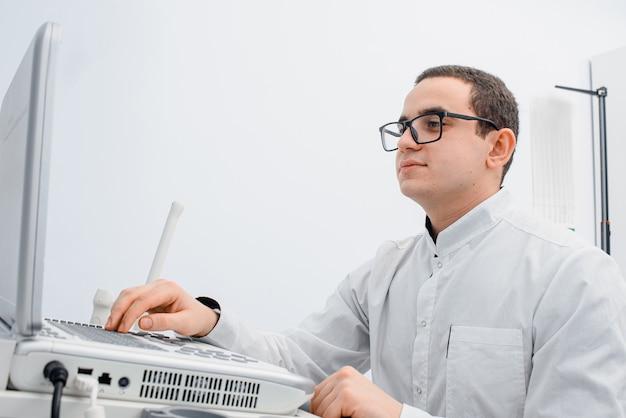 Молодой врач на рабочем месте перед аппаратом узи щитовидной железы