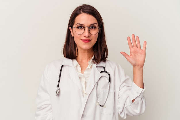 Young doctor caucasian woman isolated on white background smiling cheerful showing number five with fingers.