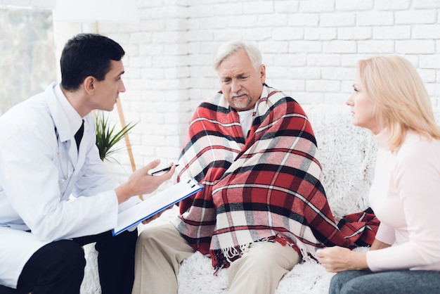 Young doctor in coat visiting old couple at home.