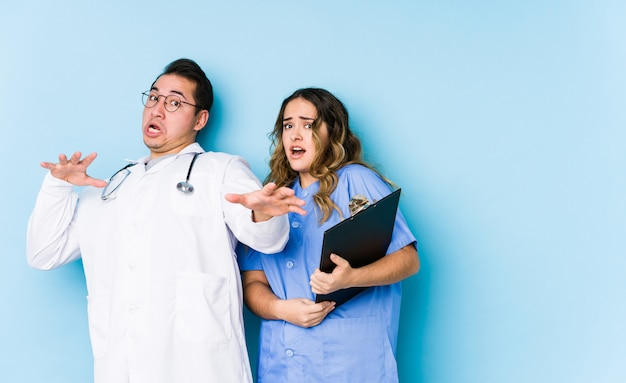 Young doctor couple posing in a blue wall isolated being shocked due to an imminent danger