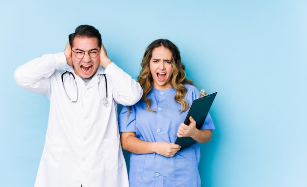 Young doctor couple posing in a blue wall isolated covering ears with hands trying not to hear too loud sound.