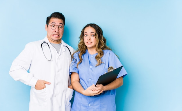 Young doctor couple posing in a blue wall isolated keeping eyes opened to find a success opportunity.