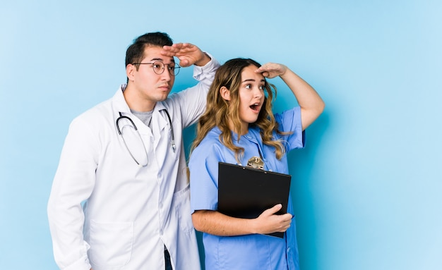 Young doctor couple posing in a blue wall isolated looking far away keeping hand on forehead.