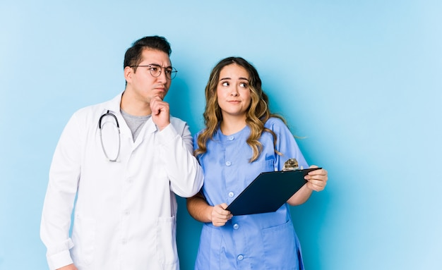 Young doctor couple posing in a blue wall isolated looking sideways with doubtful and skeptical expression.