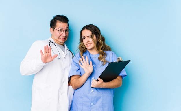 Young doctor couple posing in a blue wall isolated rejecting someone showing a gesture of disgust.