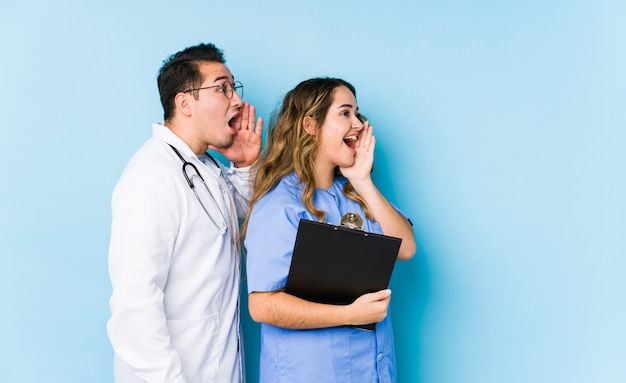 Young doctor couple posing in a blue wall isolated shouting and holding palm near opened mouth.