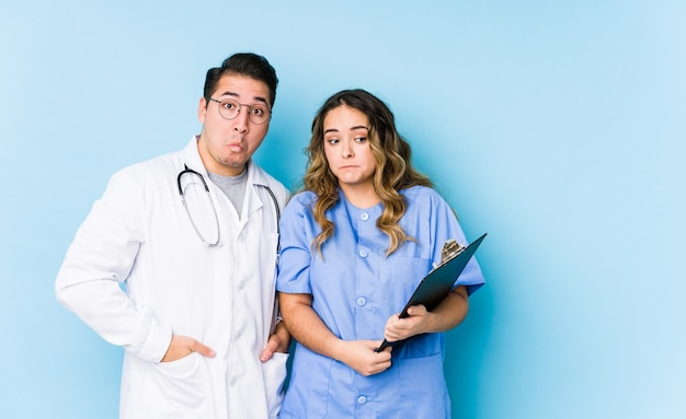 Young doctor couple posing in a blue wall isolated shrugs shoulders and open eyes confused.
