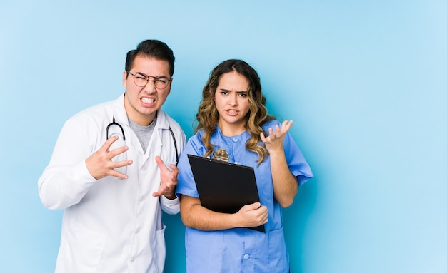 Young doctor couple posing in a blue wall isolated upset screaming with tense hands.