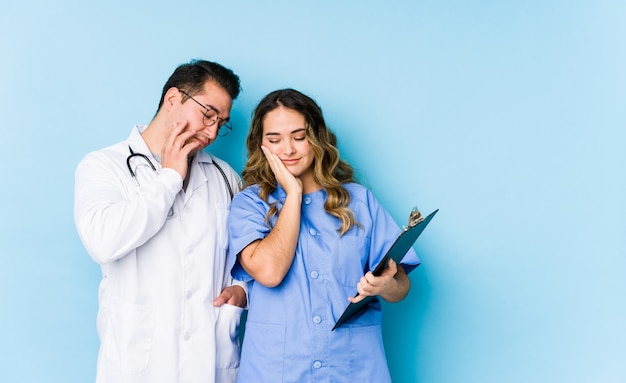 Young doctor couple posing in a blue wall isolated who is bored, fatigued and need a relax day.