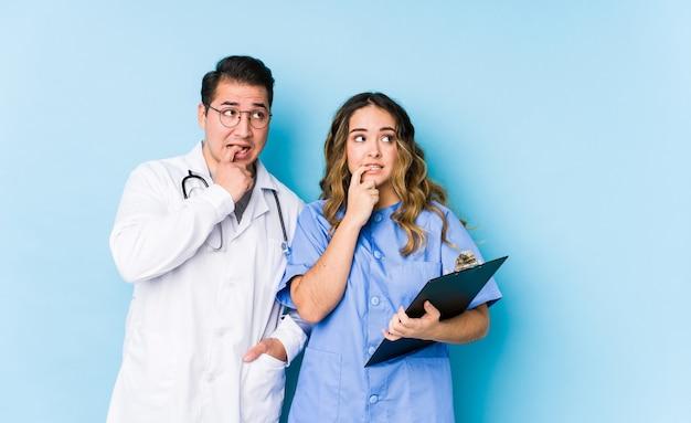Пара молодых врачей позирует в синем изолированном расслабленном мышлении о чем-то, глядя на копию пространства.
