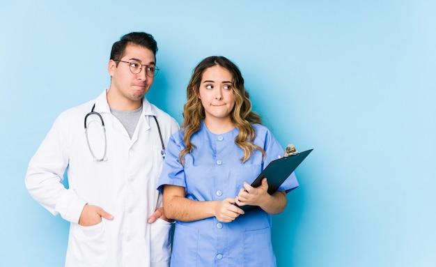 Молодая пара доктора представляя в голубой изолированной стене смущена, чувствует сомнительным и неуверенным.