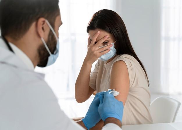 おびえた患者にワクチンを接種している若い医者