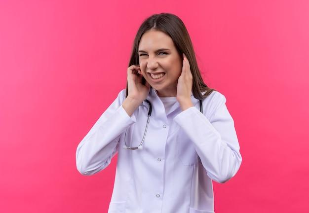 Giovane medico ragazza indossa stetoscopio abito medico orecchie chiuse sulla parete rosa isolata