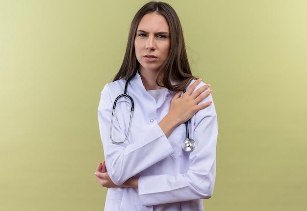 聴診器の医療用ガウンを身に着けている若い医者の女の子は、緑の壁の肩に手を置きます