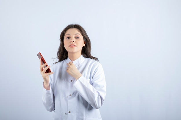 흰 벽에 핸드폰을 들고 젊은 의사.