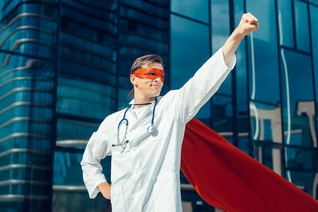 スーパーヒーローマントの若い医者は仕事の準備ができています