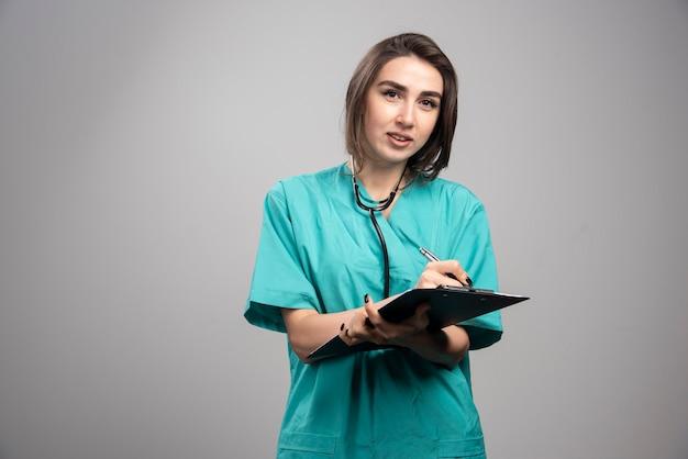 灰色の背景に立っている青い制服を着た若い医者。高品質の写真