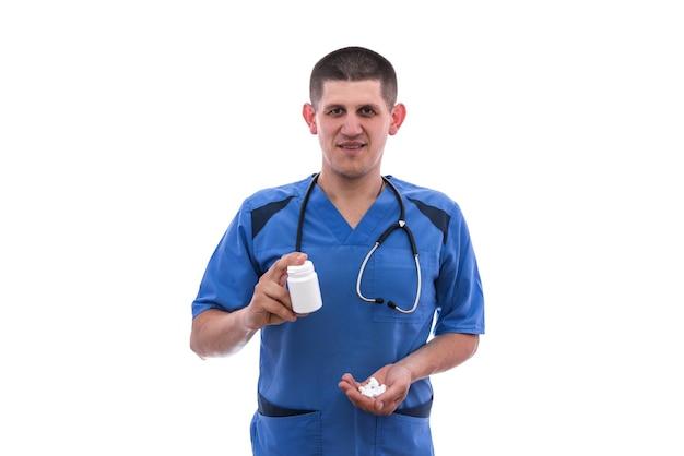 파란색 제복을 입은 젊은 의사는 흰색 배경에 격리된 항아리에서 약을 먹는다