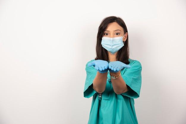 의료 마스크와 장갑 흰색 배경에 그녀의 손을 여는 젊은 의사. 고품질 사진