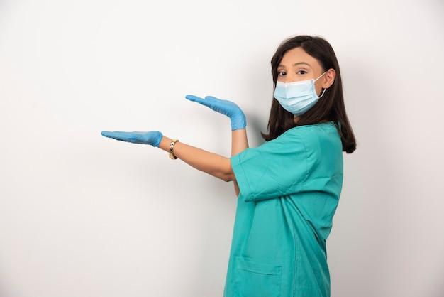 의료 마스크와 장갑 흰색 배경에 서있는 젊은 의사. 고품질 사진