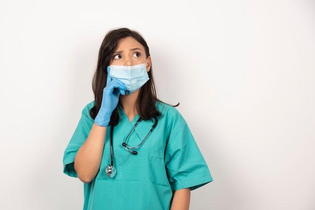 의료 마스크와 장갑 흰색 배경에 생각에 젊은 의사. 고품질 사진