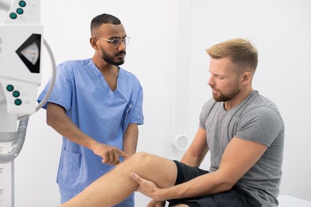 Молодой врач в униформе консультирует спортсмена, указывая на его больную ногу или колено во время визита в больницу