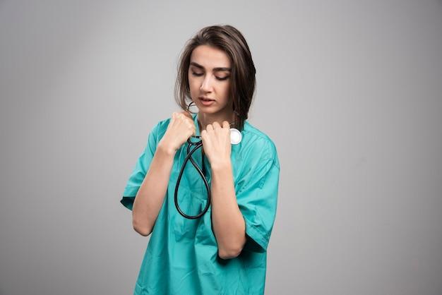 灰色の背景に聴診器を使用して制服を着た若い医者。高品質の写真