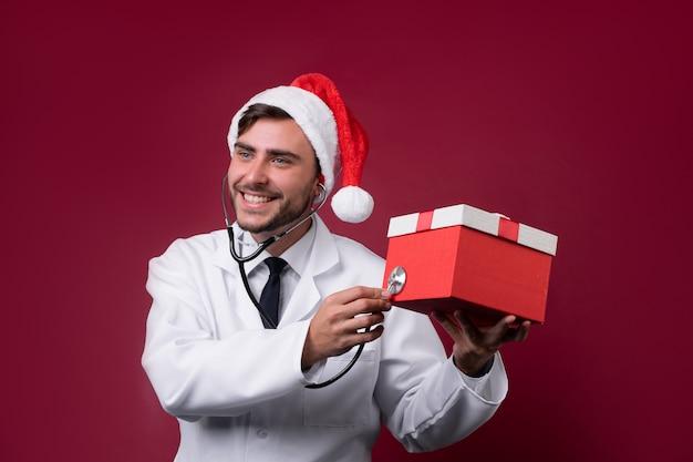 白い制服とサンタクロースの帽子の若い医者