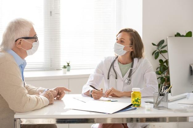 백의와 보호용 마스크를 쓴 젊은 의사는 그녀 앞에 앉아 그의 말을 듣고 처방전을 만드는 노인을 바라보고 있다